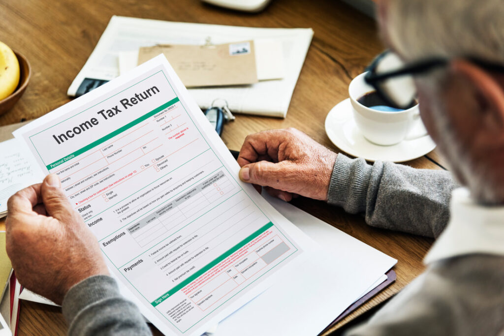Income tax rate in Italy | Old man checking income return form