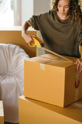 Woman wrapping up boxes | Get paid to move to Italy