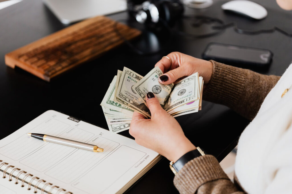 Contractor Payroll services | Woman counting money for salaries