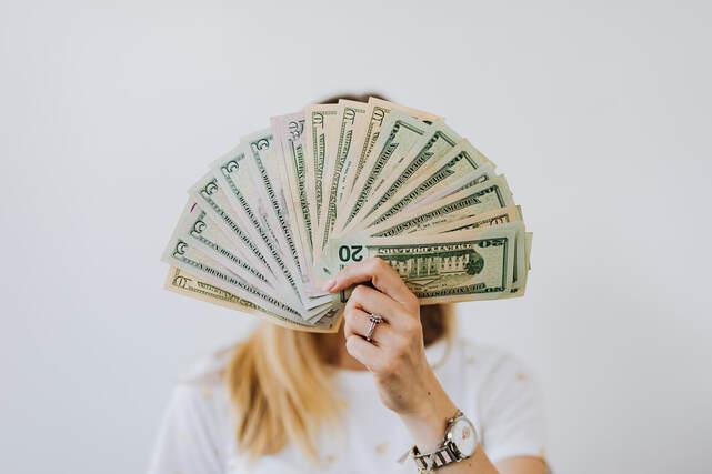 Woman showing a folding fan on money   Average salary in Italy